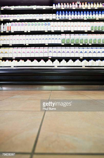 milk cartons on shelves in supermarket - milk carton stock photos and pictures