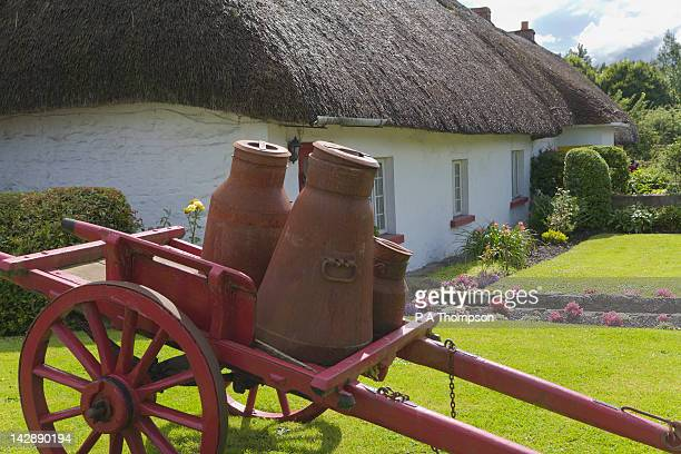Milk churns on a wooden cart outside thatched cottage, Adare, County Limerick, Ireland