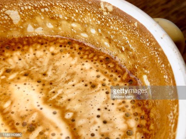 milk coffee latte froth in half full coffee cup - mediterranean culture stock pictures, royalty-free photos & images