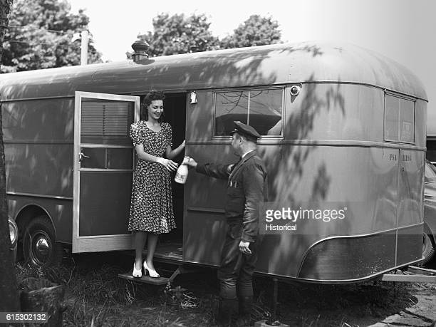 Milk delivery at a trailer in the Farm Security Administration trailer camp for defense workers in Erie Pennsylvania June 1941