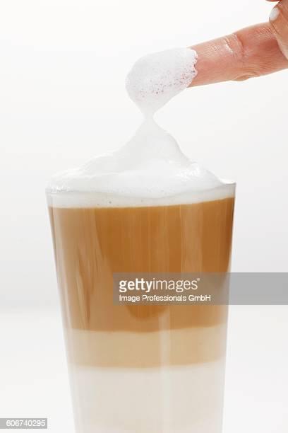 milk foam covered finger from a glass of latte macchiato - foam finger - fotografias e filmes do acervo