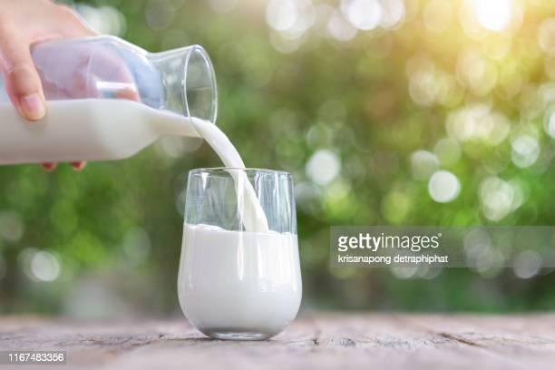 milk on a wooden table has a bokeh background,milk,milk bottle,milk glass - 注ぐ ストックフォトと画像