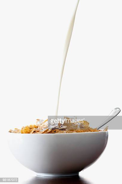 Milk pouring onto cereal in bowl
