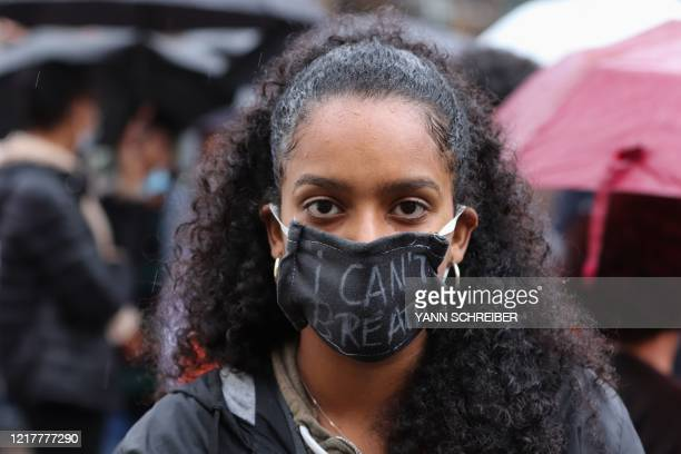 """Milka Alemsiged co-organizer of a Black Lives Matter march, poses wearing a face mask reading """"I can't breathe"""" in Frankfurt am Main, western Germany..."""