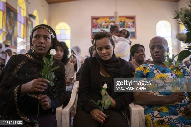 Milka Yimam who lost her 27year old son Sidrak Getachew holds a white rose beside her friend Yamrot Takleson during a special service for the...