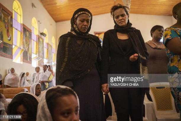 Milka Yimam who lost her 27year old son Sidrak Getachew holds the hand of her friend Yamrot Takleson during a special service for the families of the...