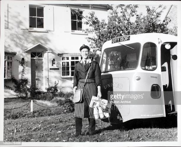 A milkman and his milk van making deliveries of milk and Cornflakes breakfast cereal in a London suburb London England