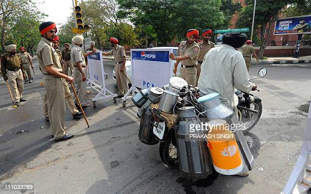 A milkman crosses a barricade as Punjab police stand guard at a road block near the Punjab Cricket Association Stadium in Mohali on March 29 2011...