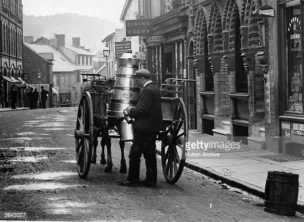 A milkman delivers milk to his customers from a milk churn in High Street Builth Wells