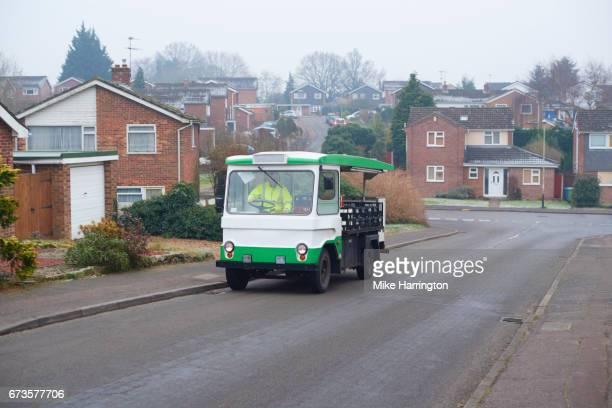 Milkman driving his milk float up an urban street