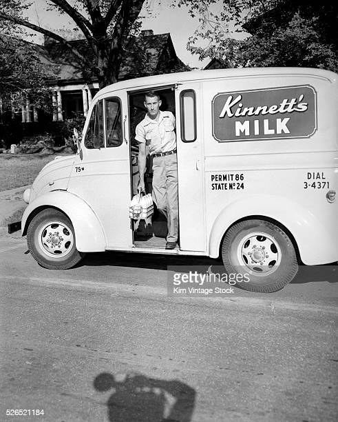 A milkman emerges from his truck on view for a shadowed photographer