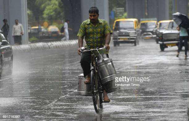 A milkman gets wet on work as it rain heavily at Matunga on Wednesday