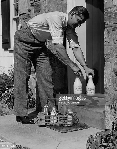 milkman leaving milk bottle on doorstep - milkman stock photos and pictures