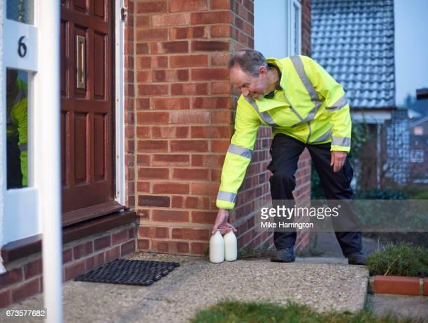 milkman leaving milk by customer's door - milkman stock photos and pictures