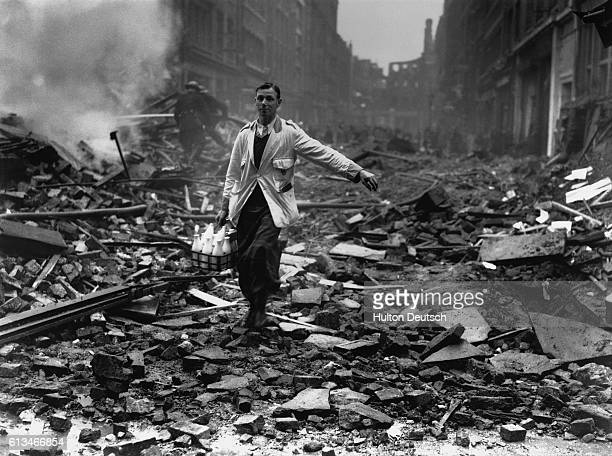 A milkman makes his normal rounds through piles of rubble after an air raid in London England