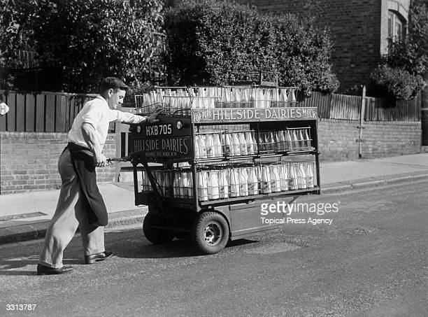 A milkman operating a handoperated electric milk float at Muswell Hill London