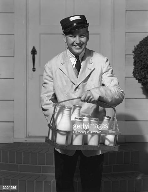 A milkman smiles while holding a tray with milk bottles of varying sizes at the front door of a home 1950s He wears a cap and jacket