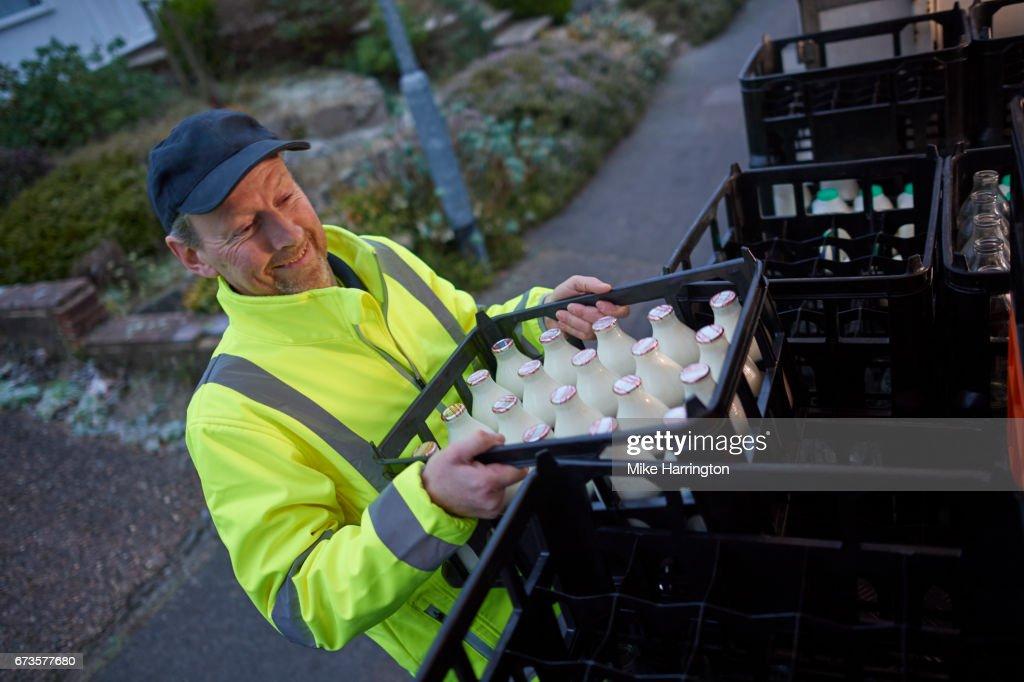 Milkman unloading his milk float in early morning : Stock Photo