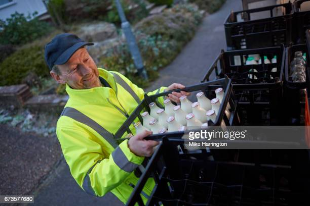 milkman unloading his milk float in early morning - milkman stock photos and pictures