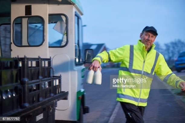 Milkman walking away from his milk float with milk bottles in hand