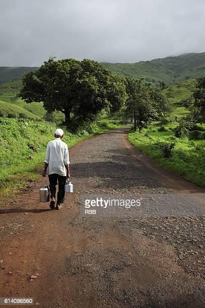 Milkman Walking on a Village Road