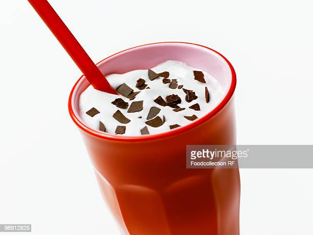 Milkshake with flakes of chocolate in red glass, close-up