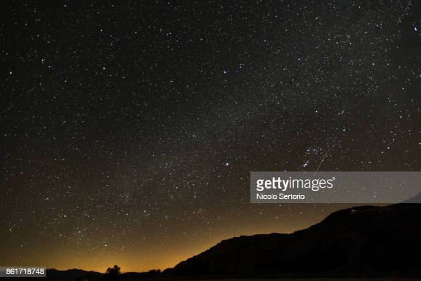 milky way and city lights from the mojave desert - カリフォルニア州ベーカー ストックフォトと画像