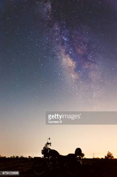 Milky Way and starry night over land and motorcycle silhouette