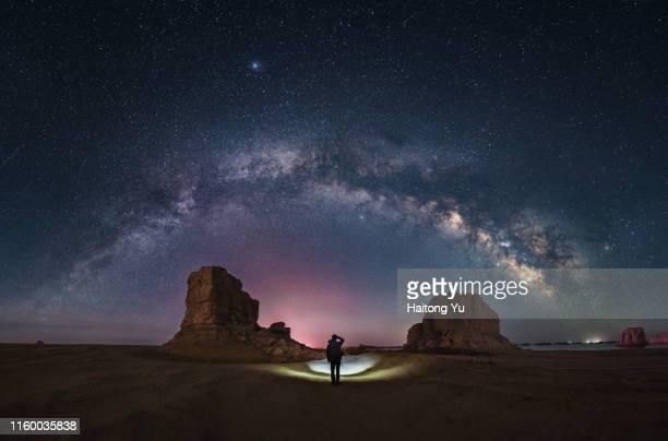 milky way and stars over rugged terrain. qinghai, china - felsbogen stock-fotos und bilder