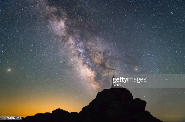 milky way. night sky and silhouette of a standing man - ideas stock pictures, royalty-free photos & images