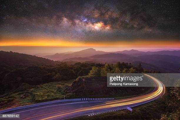 Milky way on the top mountain and road at front in intanon mountain , most tallest mountain in Chiangmai , Thailand