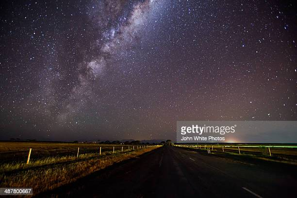 milky way over a rural road. south australia. - country road stock pictures, royalty-free photos & images