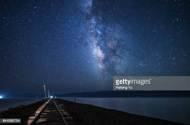 Milky way over abandoned railway track in the middle of salt lake.