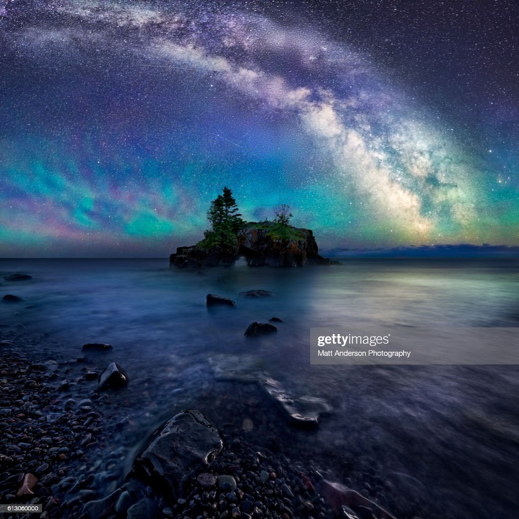 Hollow rock is an iconic coastal formation located on the North West side of Lake Superior. Air glow creates a colorful luminescent atmosphere below the night sky and Milky Way. A long exposure captures the faint stars and creates a smooth watery surface atop Lake Superiors churning sea.