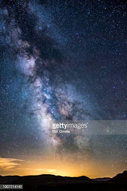 milky way over night pollution and mountains, spain - milky way stock pictures, royalty-free photos & images