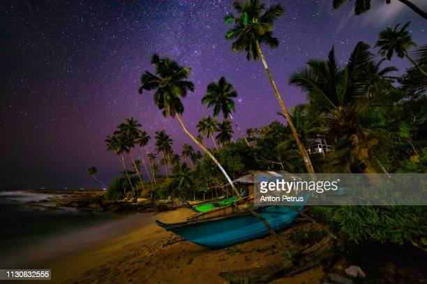 Milky Way over the sandy beach with boats and palm trees. Sri Lanka