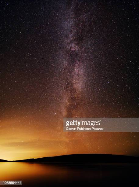 milky way over water - solar system stock pictures, royalty-free photos & images