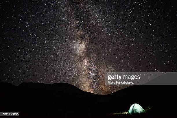 Milky way rises above illimunated tent in mountain
