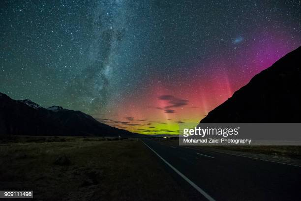 milky way rising above highway near tekapo new zealand with aurora australis or the southern light lighting up the sky - new zealand foto e immagini stock