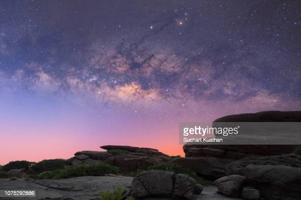 milky way stars shine over rock fields at grand canyon of thailand (sam phan bok). - orbiting stock pictures, royalty-free photos & images