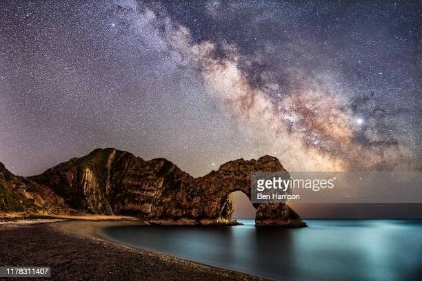 milkyway in dorset over durdle door at the jerassic coast beach - sunset stock pictures, royalty-free photos & images