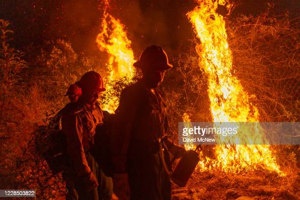 Mill Creek Hotshots set a backfire to protect homes during the Bobcat Fire on September 13, 2020 in Arcadia, California. California wildfires that...