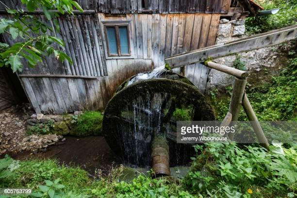 mill wheel and waterway at dilapidated building - mulino ad acqua foto e immagini stock