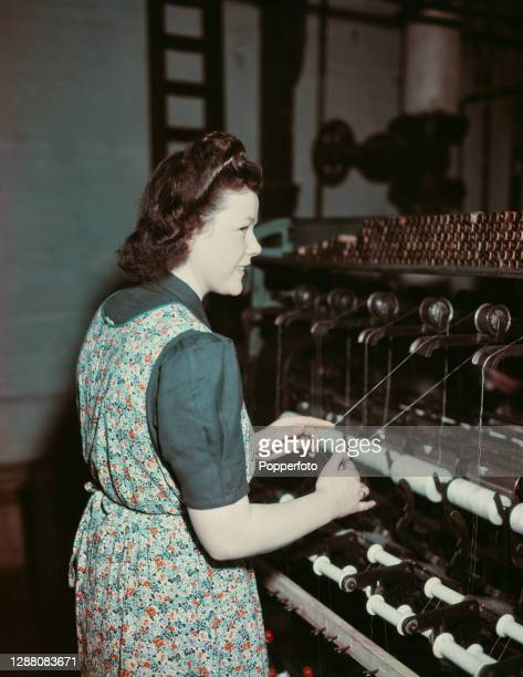 Mill worker Kathleen McGowan operates a ring spinning machine on a long frame at Lister Mills in the Manningham district of Bradford, West Yorkshire,...