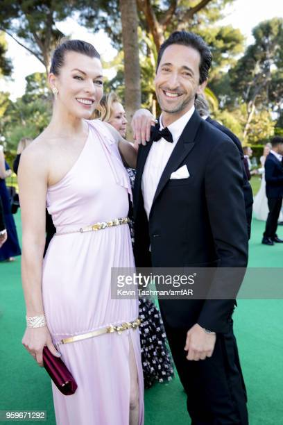 Milla Jovovich and Adrien Brody attend the cocktail at the amfAR Gala Cannes 2018 at Hotel du CapEdenRoc on May 17 2018 in Cap d'Antibes France