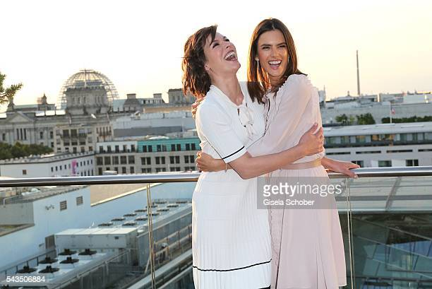 Milla Jovovich and Alessandra Ambrosio laugh during the after party of the Marc Cain fashion show spring/summer 2017 at China Club on June 28 2016 in...