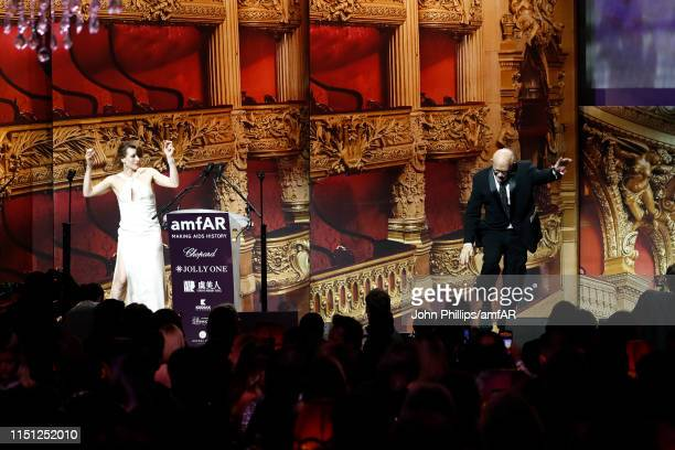 Milla Jovovich and Bill Roedy speak on stage during the amfAR Cannes Gala 2019 at Hotel du Cap-Eden-Roc on May 23, 2019 in Cap d'Antibes, France.