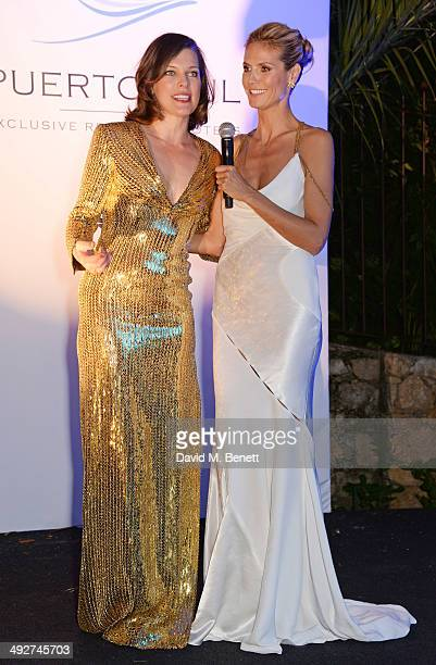 Milla Jovovich and Heidi Klum speak at the welcome party for Puerto Azul Experience Night at Villa St George on May 21 2014 in Cannes France