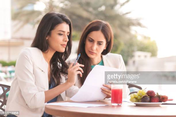 Millenial Arab Businesswomen Reviewing Contract During Business Lunch at Hotel