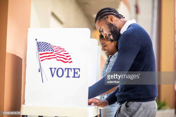 millenial black man and woman voting in election - voting stock pictures, royalty-free photos & images